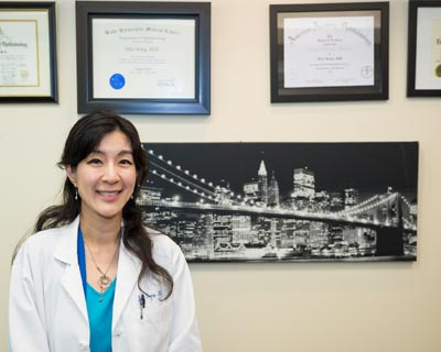 Dr. Song stands with her diplomas in her office.