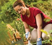 Woman gardening while wearing eye protection