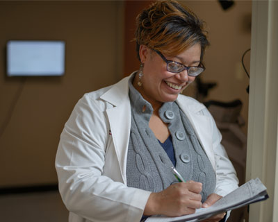 Chasidy Singleton, MD, takes notes in Nashville General Hospital, after treating Peggy Wellman for glaucoma.