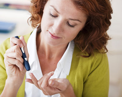 Woman testing blood sugar with glucose meter and drop of blood on fingertip
