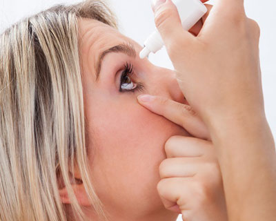 Woman putting eye drops in eye