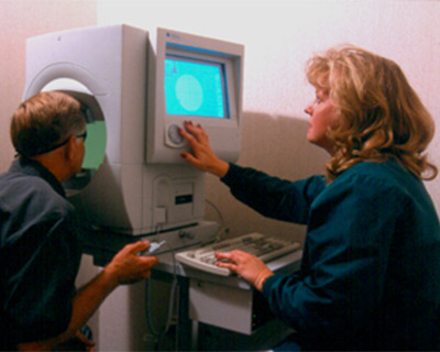 A patient sits at a perimeter machine taking a visual field exam.