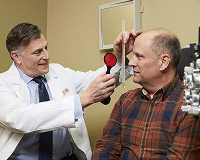 Stephen Lipsky, MD, performs an eye exam on a patient in his office